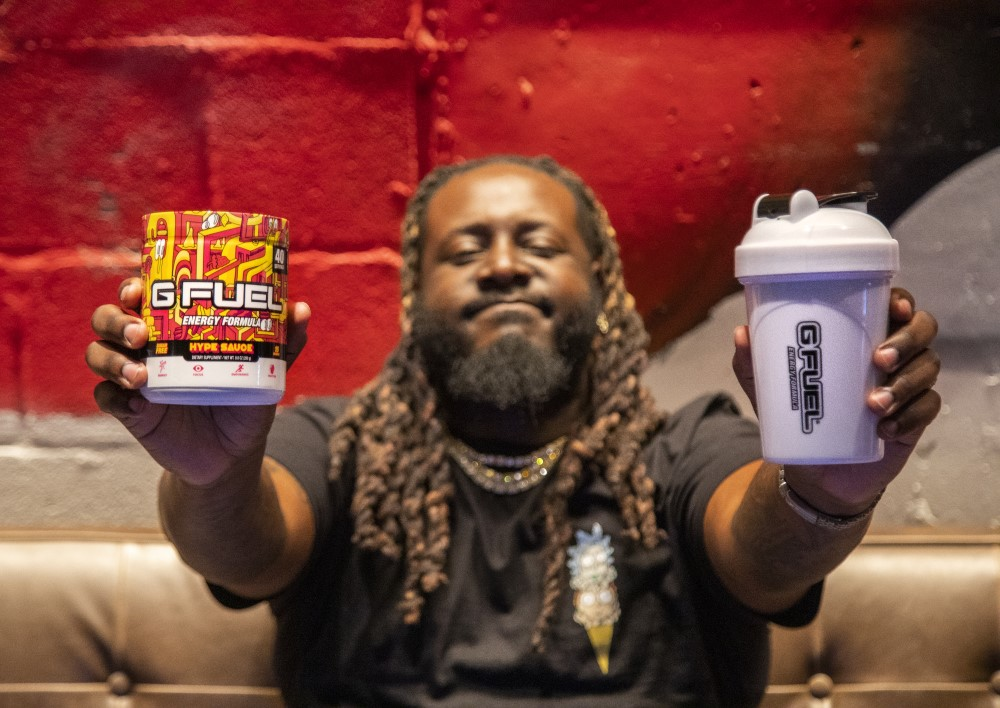 t-pain holding a g fuel hype sauce tub and hype sauce shaker cup
